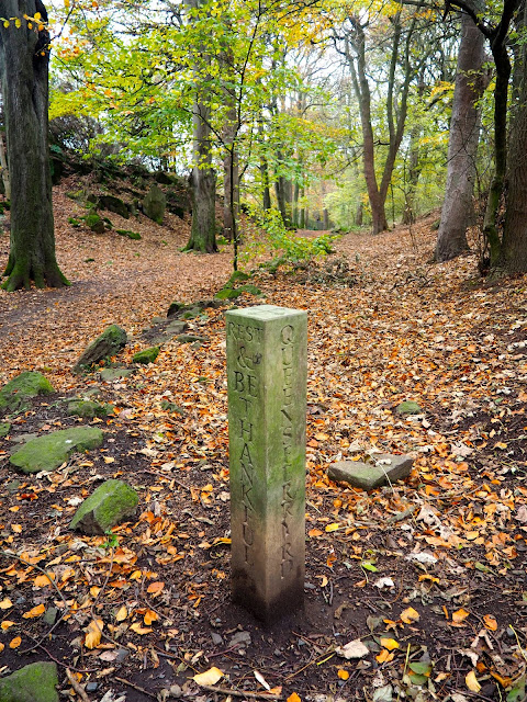 Hiking path stone marker in autumn woodlands on Corstorphine Hill, Edinburgh, Scotland
