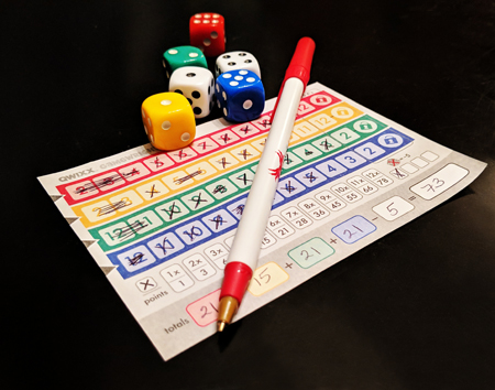 image of a Qwixx game card, filled out after a completed game, pictured on my dining room table along with a pen and colorful dice