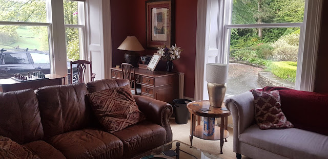 Guest Lounge is decorated with comfortable looking couches and matching brown wooden furniture.