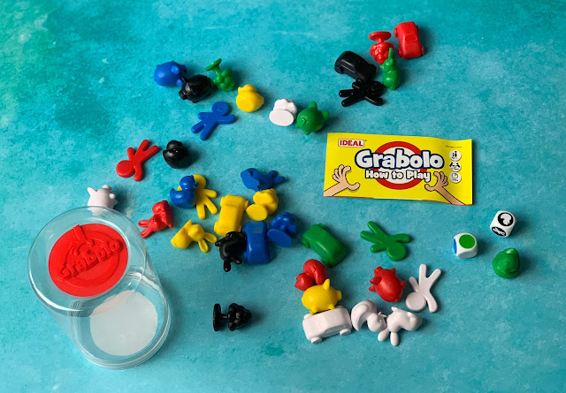 Different shape plastic pieces in white, yellow, red, green, blue, black and yellow and 2 dice next to instructions for How to Play Grabolo