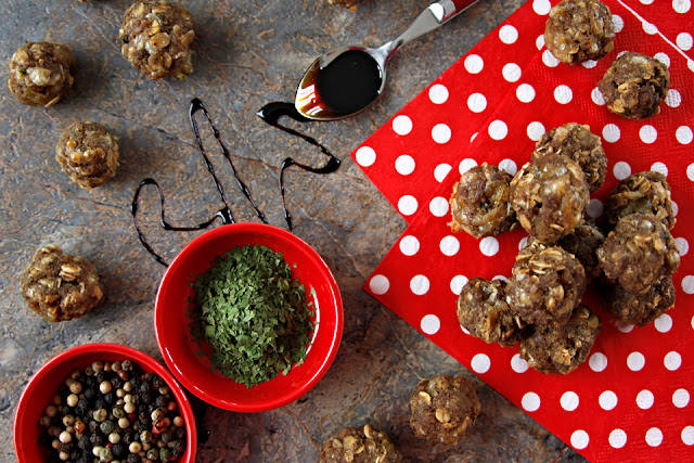 Meatballs on a stone table with red bowls of spices and polka dot napkins.