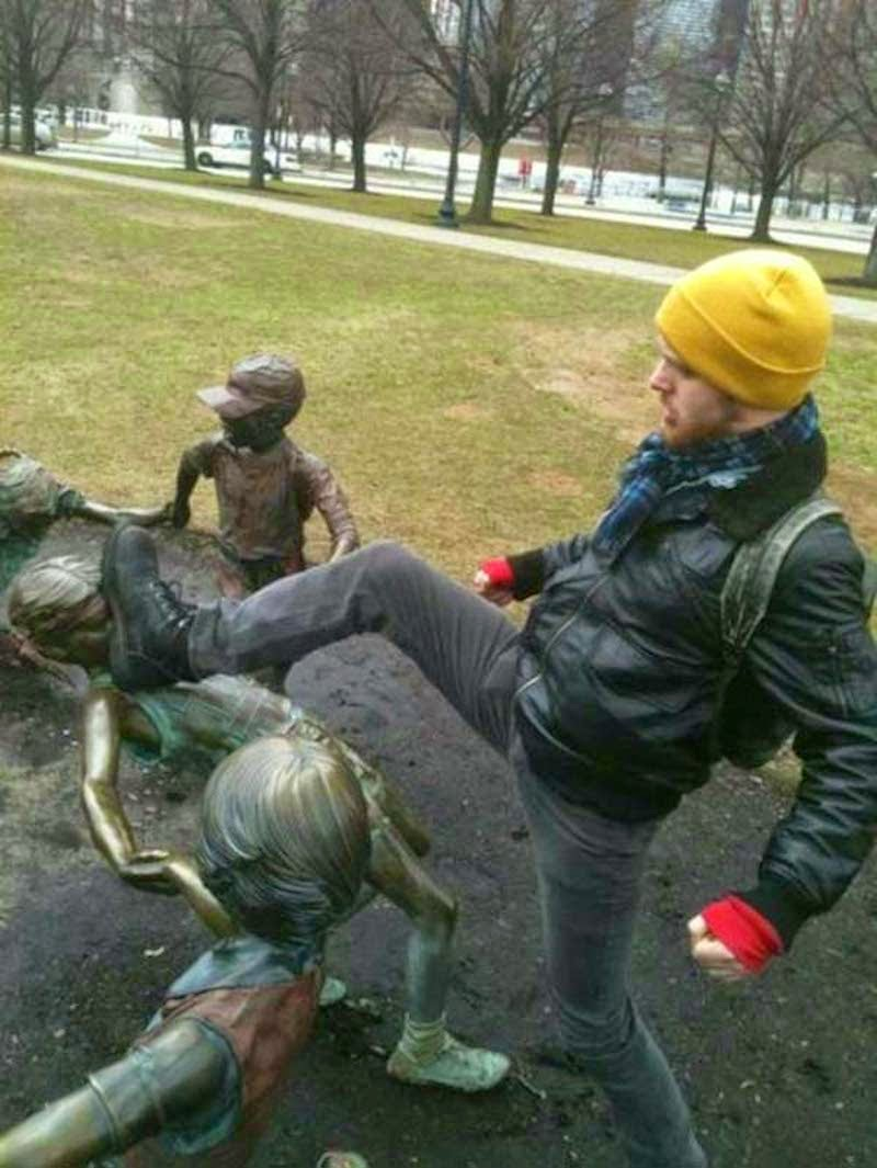 15. Note to the man wearing a yellow beanie: picking on statue children does not make you look tough.  - 23 Times Pedestrians Messed With Statues...And It Was Downright Hilarious