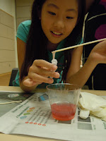 Girl examining light red liquid in a plastic cup