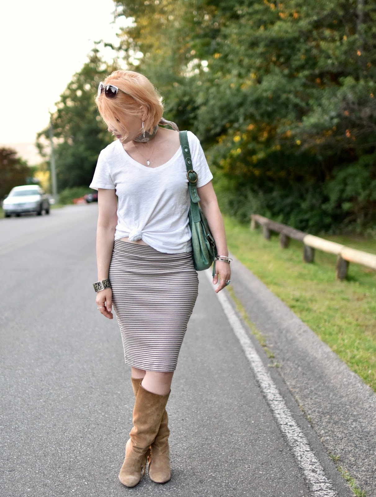 styling a striped tube skirt with a waist-tied tee, fringy boots, and a bandana