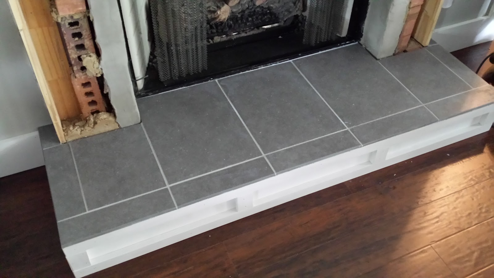 Deck our home fireplace tutorial 2 installing hearth tile i did grout between the tile and the black fireplace insert but didnt worry about the area where i would be installing mosaic tile and wood dailygadgetfo Choice Image