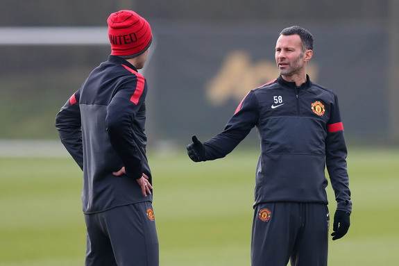 Ryan Giggs talks with a Manchester United teammate during a training session at Carrington