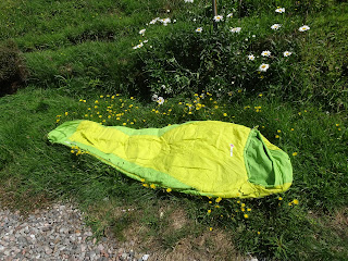 unwrapped sleeping bag on grass ready for camping