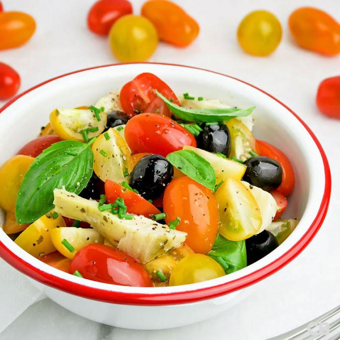 Salade van verschillende soorten cherrytomaatjes, artisjokkenharten en olijven