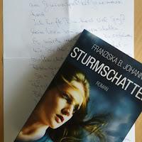 Das Cover zeigt ein Mädchen vor einem düster-blauen Himmel, ihre Haare wehen im Wind
