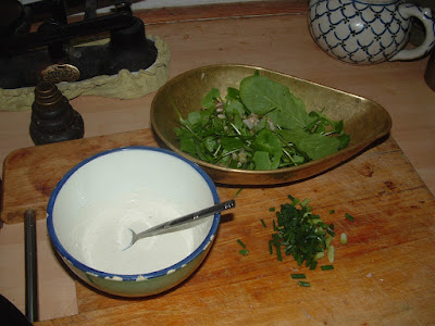 A bowl of dressing with a spoon, a weighing bowl with salad greens, and chopped spring onions on a wooden board