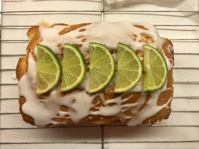 Gin & tonic cake with drizzled icing and slices of lime