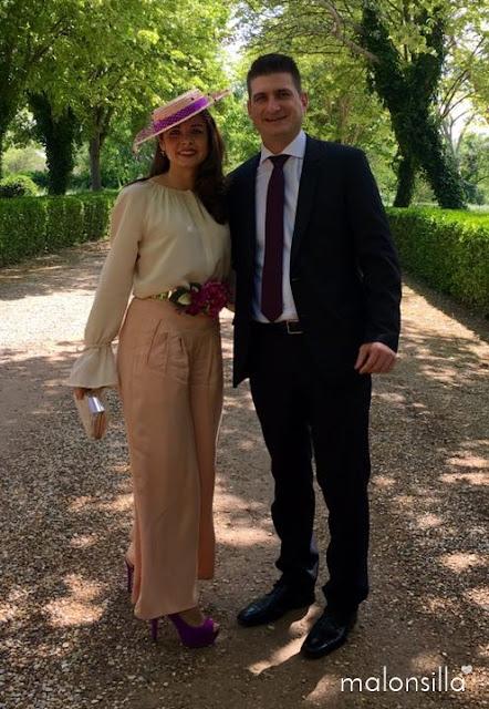 Invitada boda con sombrero canotier de ala ancha y copa baja color cardenal, pantalon rosa nude y blusa color crudo