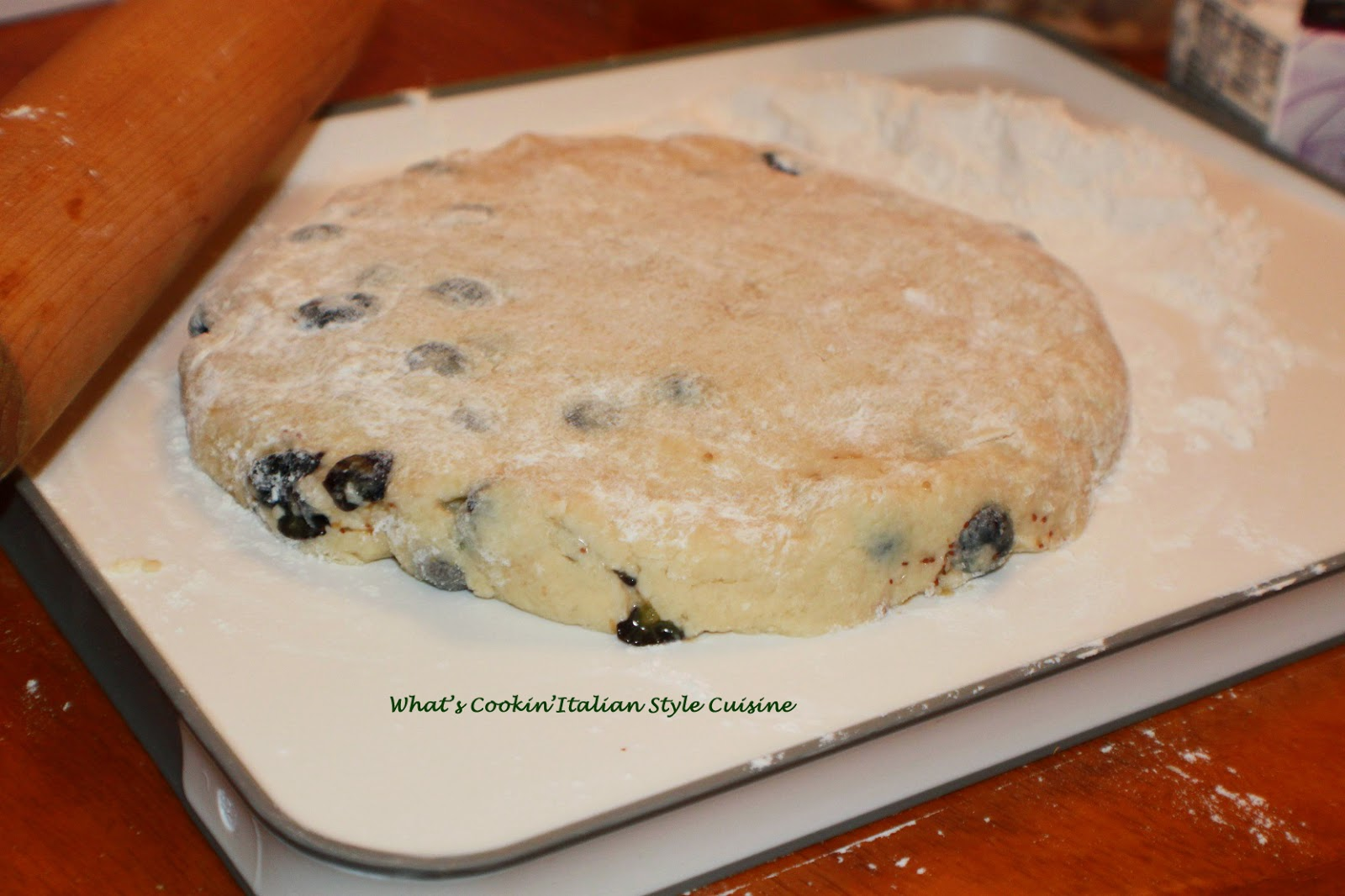 This is the dough rolled out to make these almond blueberry delicious homemade buttery flavored baked biscuits called scones. These have blueberries in them with a drizzle of thin frosting over the top with slivered almonds. They are usually eaten at breakfast time in European pastry shops