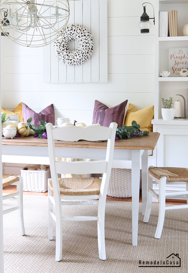 dining room with sitting bench, orb chandelier and plum and mustard tablescape