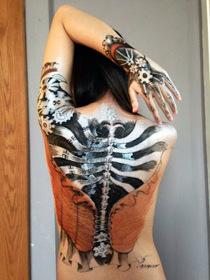 Woman with her back painted with a steampunk skeleton and corset and gloves. Steampunk body painting