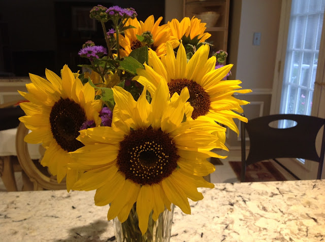 beautiful sunflowers and purple flowers in a vase