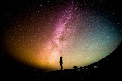 Una persona en medio de la oscuridad mira el firmamento que está iluminado por colores diversos y estrellas.