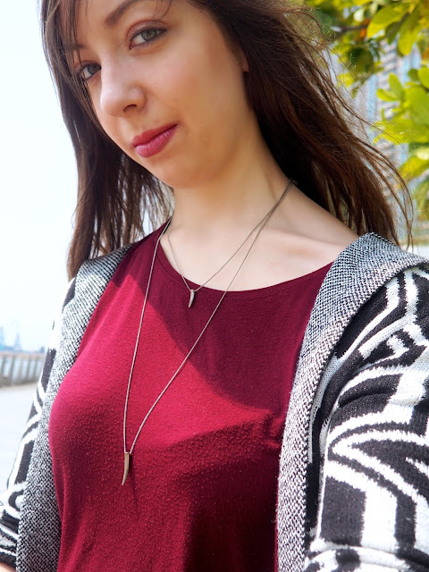 Kicking Back - outfit close up jewellery details of black and white print cardigan, red top, and silver fang layered pendant necklaces