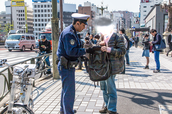 Japanese passerby gets questioned and searched by a policeman.