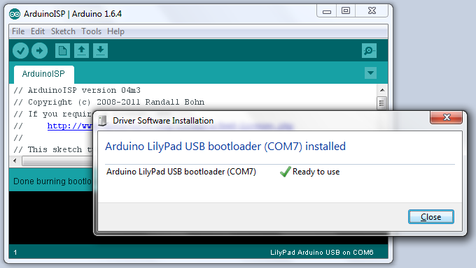Screenshot.  Foreground: The bootloader have been downloaded. Windows have successfully recognized the Arduino LilyPad USB, and installed the driver for it.  Background: ArduinoISP sketch which was running on Arduino Mini-Pro.
