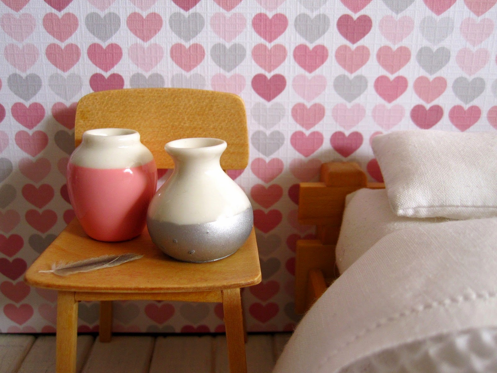 Modern dolls' house miniature bedroom scene with futon bed with a white waffle-weave blanket, a blonde-wood chair holding two dip-painted white vases and a feather.