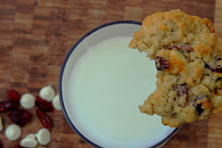 oatmeal cranberry white chocolate chip cookie with a bite out of it on the edge of a glass of milk