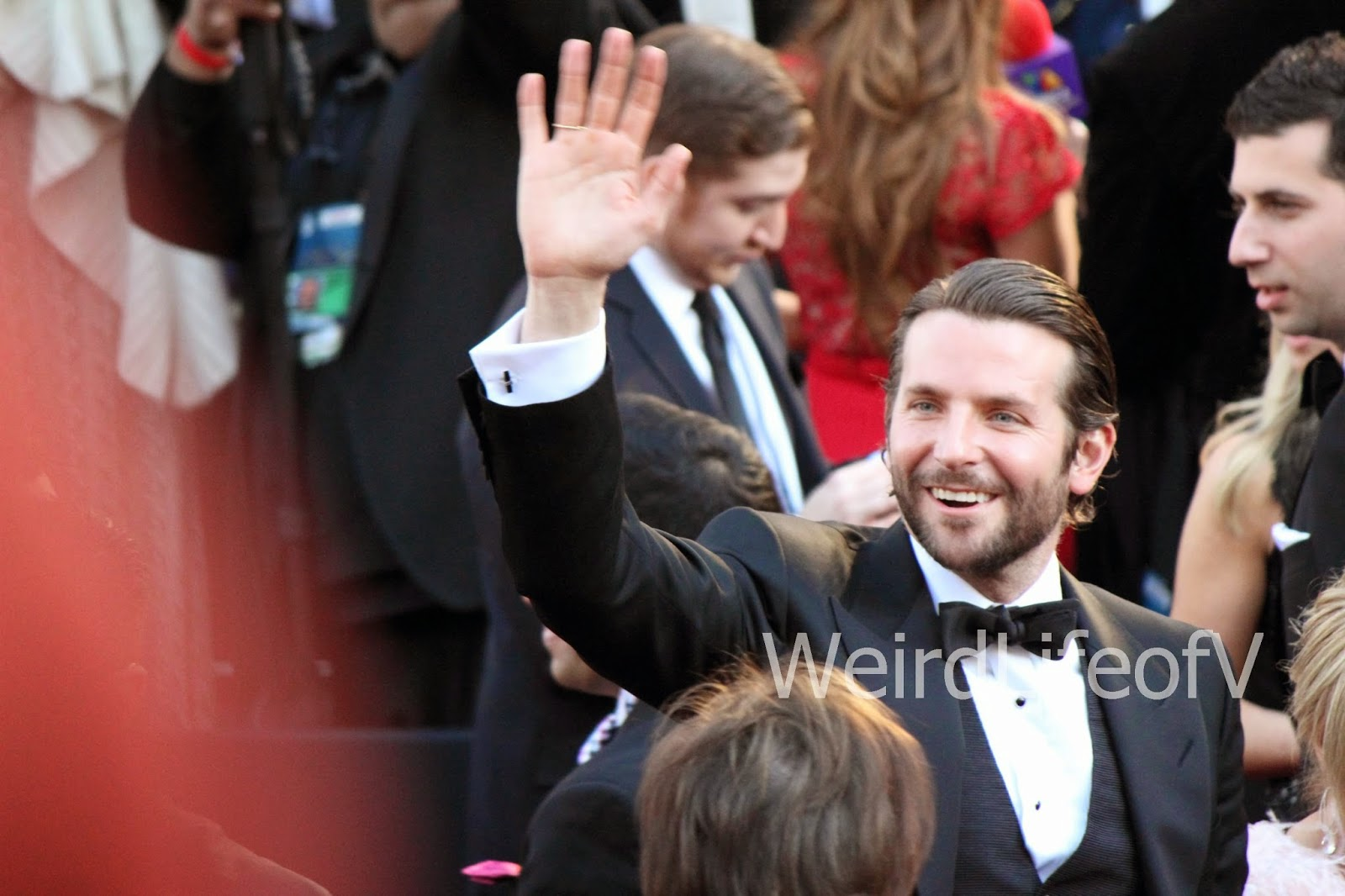 Bradley Cooper waves to the fans on the red carpet for the 2013 Oscars