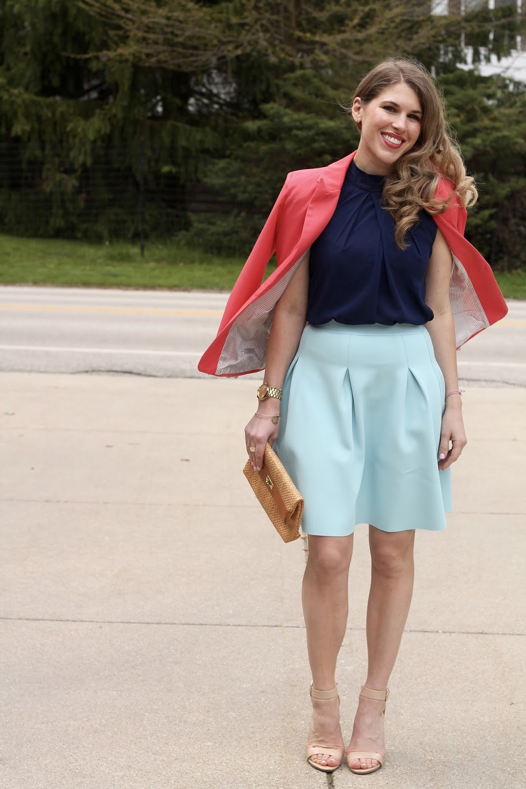 Navy blouse, light blue scuba skirt, coral blazer, nude heels, straw clutch