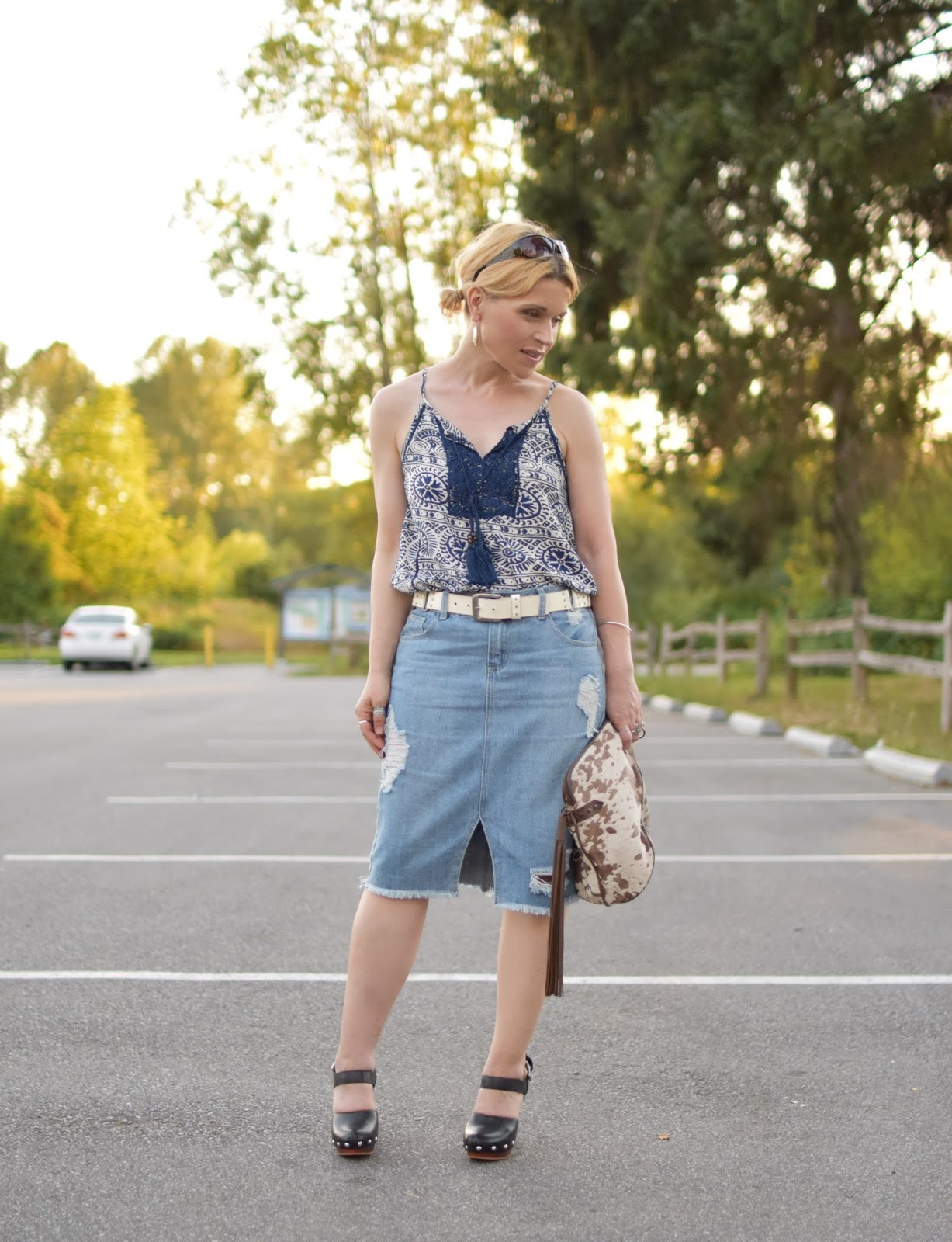 Monika Faulkner styles a distressed denim midi-skirt with a peasant tank top, Vince Camuto heels, and pony-hair bag