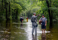 A U.S. Air Force member assigned to the South Carolina Air National Guard assists citizens during evacuation efforts after Hurricane Florence hit in September 2018. (Credit: U.S. Army National Guard via Getty Images) Click to Enlarge.