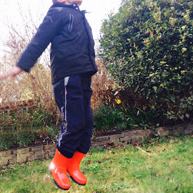 Boy in red wellington boots jumping in a park with a grey sky over head - Tip five tips for helping autistic kids in wet weather