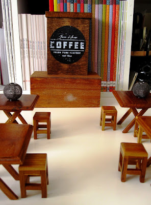 Various one-twelfth scale stools and tables arranged on a desktop, with a wooden counter with the word 'Coffee' on it at the back.