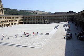 A birds eye shot of a grand rectangular stone coloured buiding overlooking a light stone covered area with metal chairs and tables