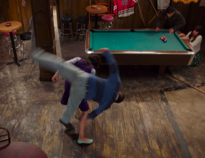 Janet is in the middle of flipping the demon from the last picture. Both of his legs are in the air and his body is sideways. Tahani and Jason are cowering behind the pool table.
