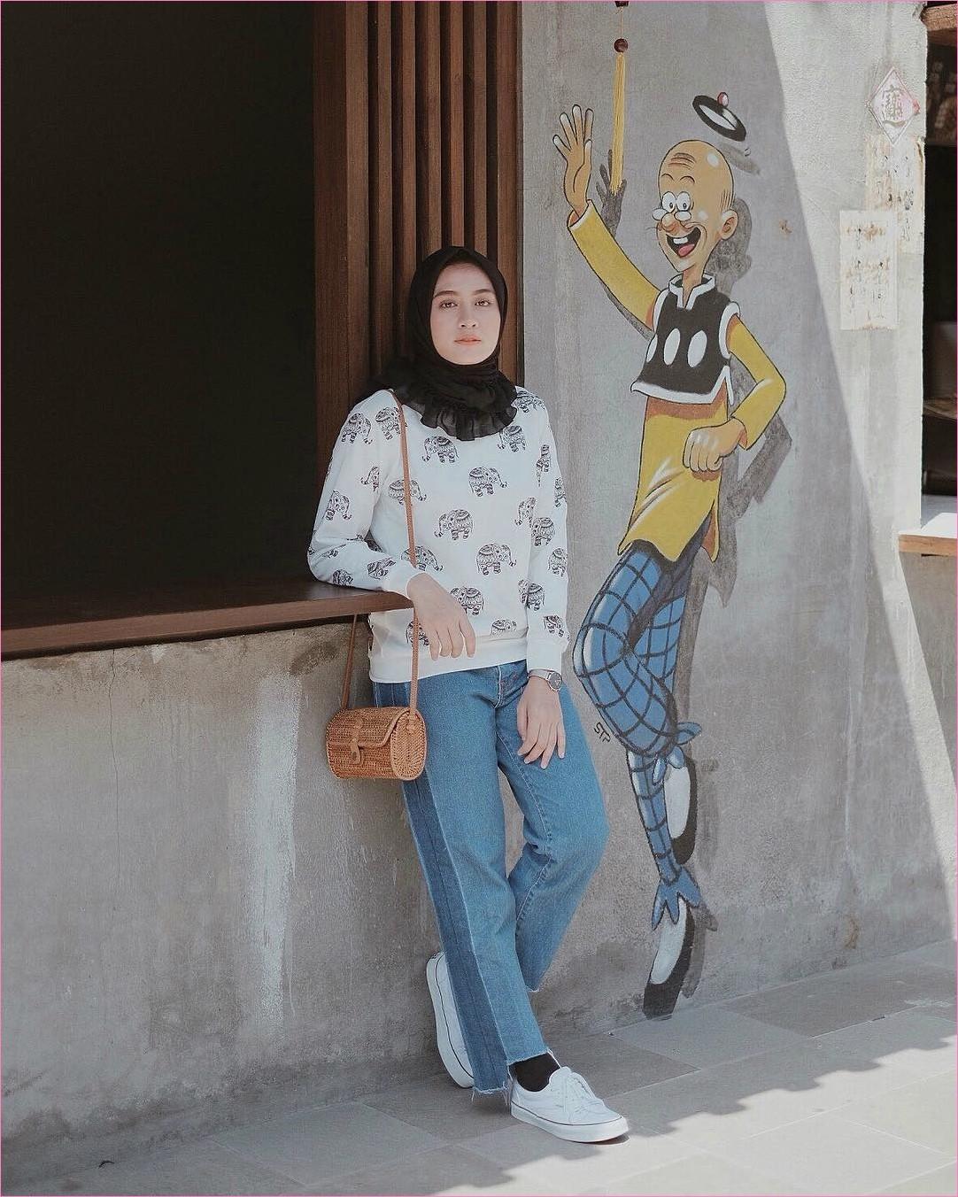 Outfit Baju Hijab Casual Untuk Kuliah Ala Selebgram 2018 jean pallazo denim kaos kaki hijab segiempat hitam sweater blouse bermotif gajah sneakers kets putih sling bags rotan jam tangan bulat abu gaya casual kain sutra katun rayon ootd outfit 2018 selebgram jendela kayu gambar kartun