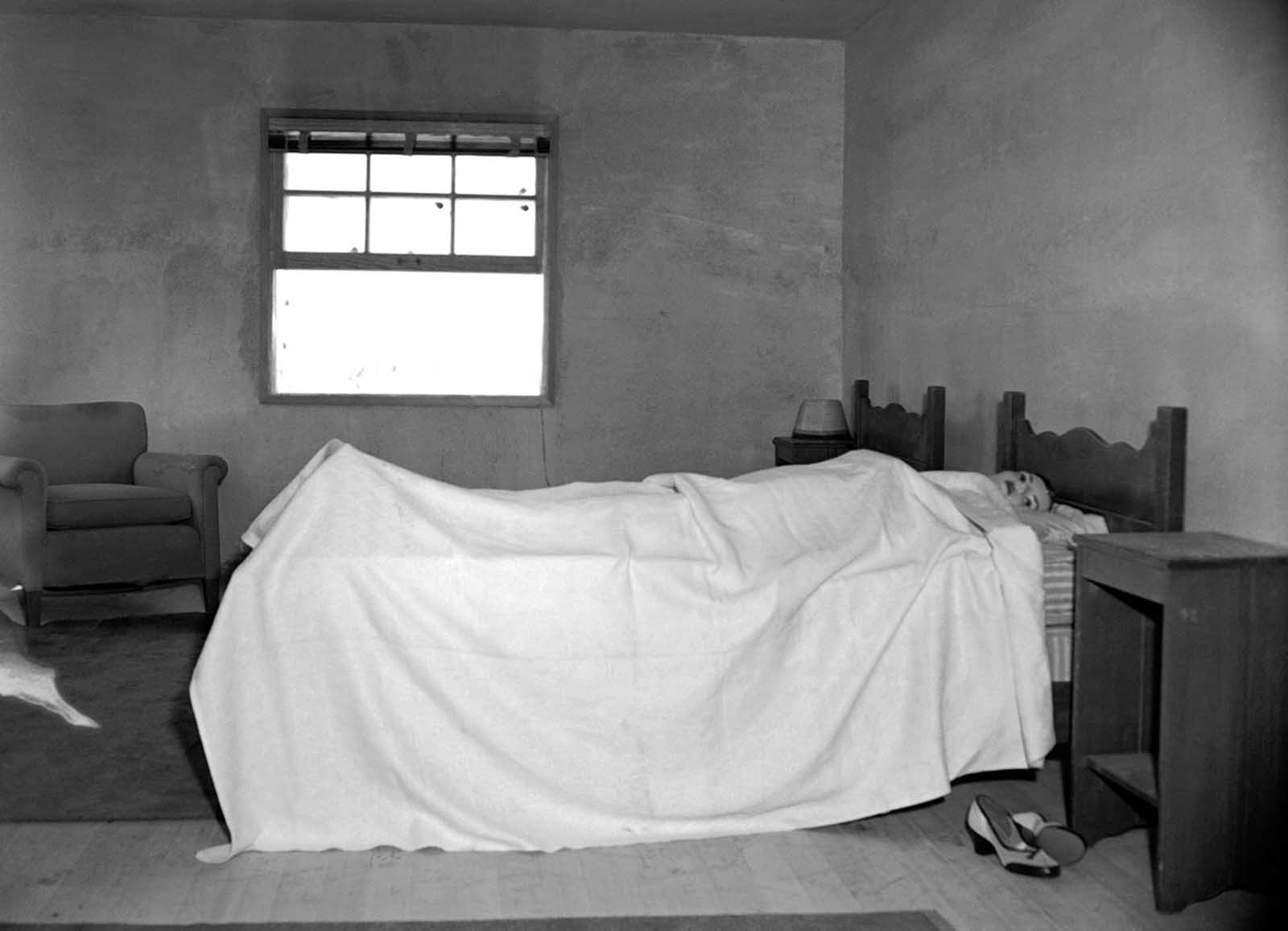 (1 of 2) Stretched on a bed, in an upstairs bedroom of House No. 2, is a mannequin ready to test the effects of an atomic explosion at the atomic proving grounds near Las Vegas, Nevada, March 15, 1953. Through the window a mile and a half away stands a 300-foot steel tower atop which the bomb will be detonated. The purpose of the test blast is to show Civil Defense officials what would happen in an American city if it were subjected to a atomic attack.