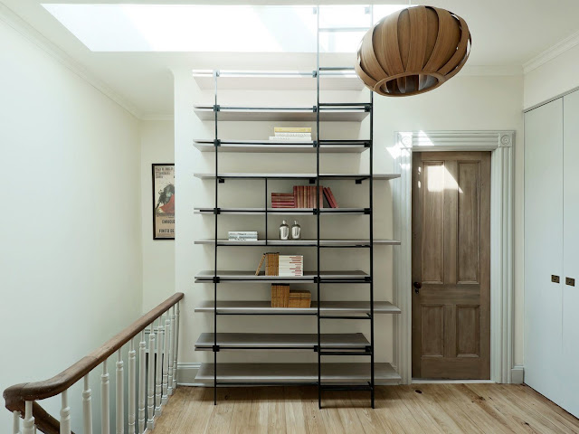 Gray floating shelves with a black ladder going up to a skylight