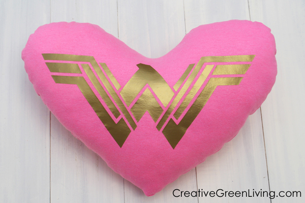How to turn an upcycled t-shirt into a pillow. Hot pink heart shaped pillow with gold wonder woman symbol centered on it.