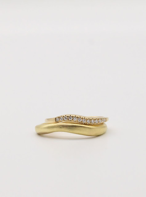 Custom wedding set in 18k Yellow Gold. Womens band features pave set white diamonds. Mens textured band.