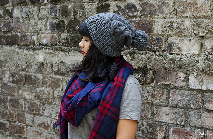 Image of a young woman wearing a grey outfit and plaid scarf with red lips and a wool beanie hat over a straight lob hairstyle on a brick background