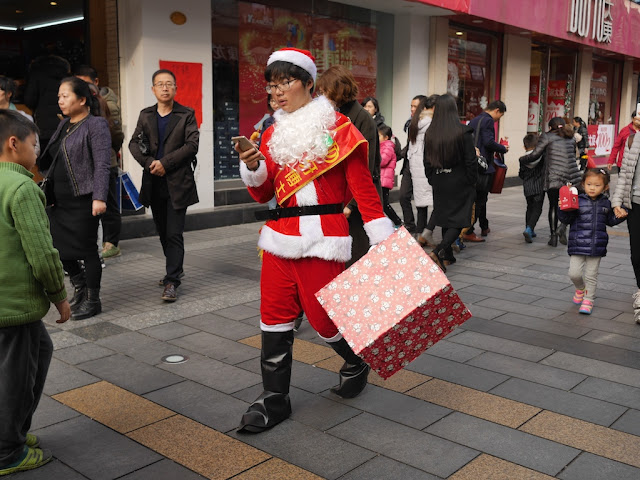 person in Santa outside looking at their mobile phone while walking