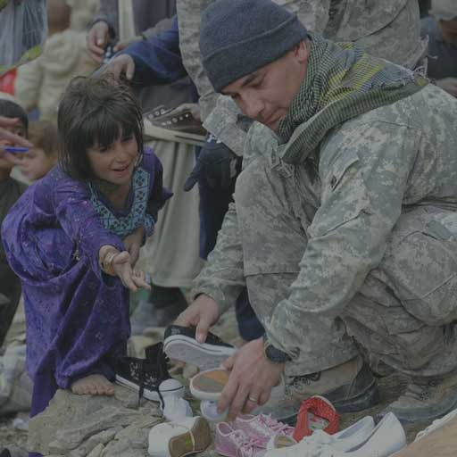 Soldier giving child shoes