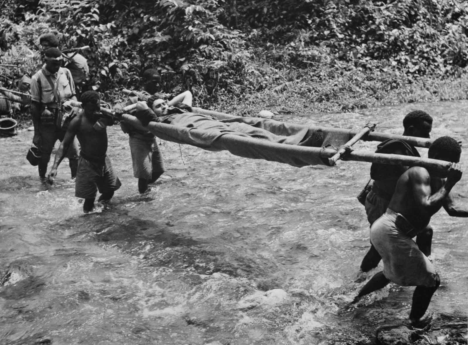 Stretcher bearers evacuate a wounded Australian soldier following a battle at Kokoda.