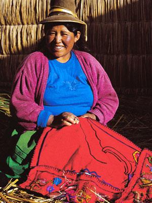 Foto de una mujer puneña bordando y sonriendo