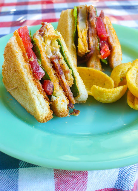 Fried Green Tomato BLT Club Sandwich, three slices of sandwich white bread toasted and layered in between with perfectly fried green tomatoes with crispy bacon for the first layer and a  perfectly ripe beefsteak tomato with crispy bacon for the second layer.  Two classic sandwiches gloriously combined into one Epic sandwich cut into quarters and held together with toothpicks!