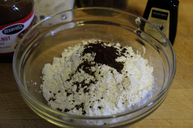 Instant coffee being added to the mixing bowl with the sugar.