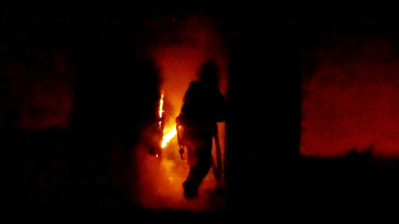 A firefighter silhouetted against the fire inside the residence