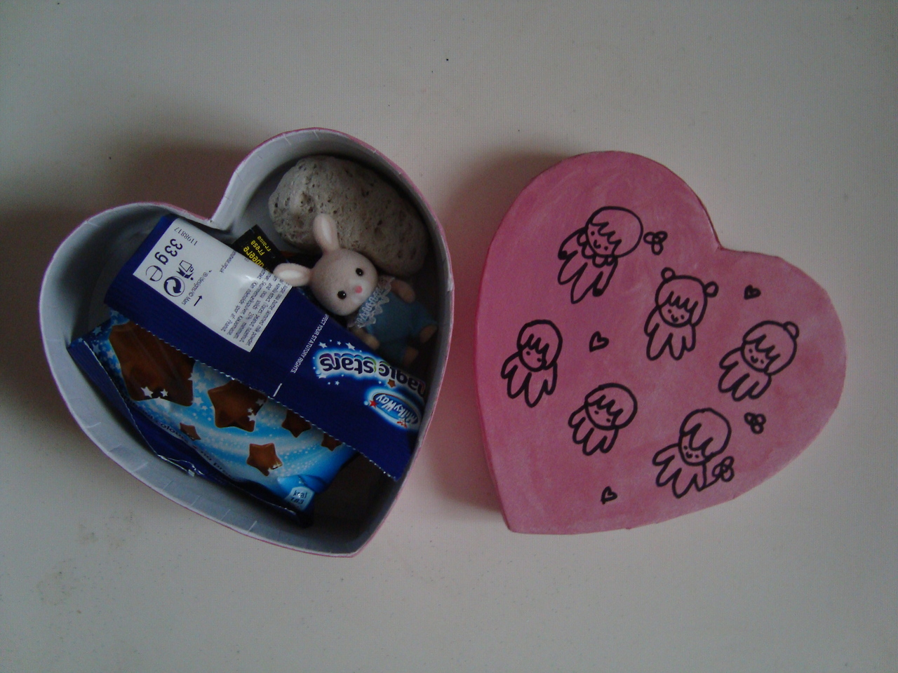 A heart shaped box lies open, showing chocolate stars and a toy bunny inside.