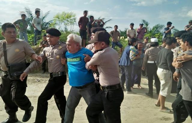 Polisi mengamankan warga yang menahan truk pengangkut milik PT VSC.