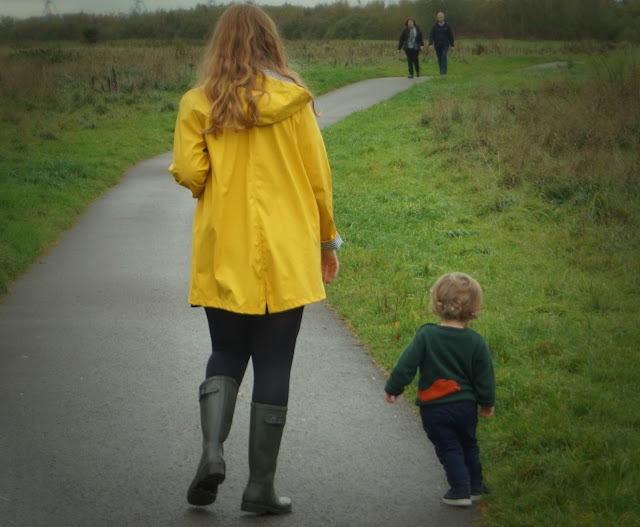 toddler son and mother walking away from the camera on a path through a country park. A couple approaches them in the distance